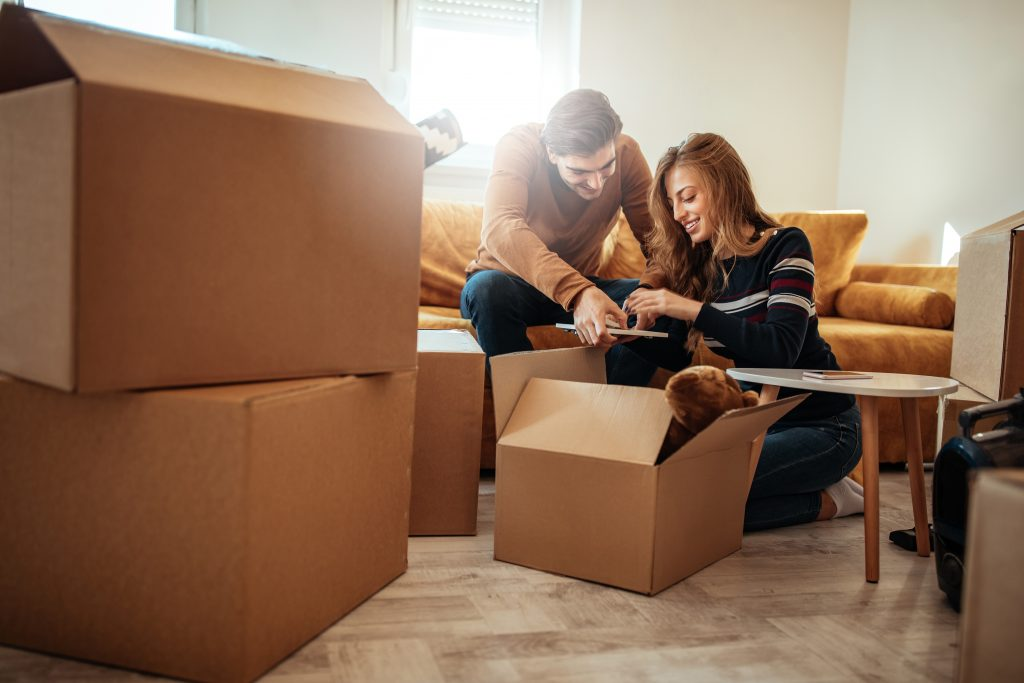 Couple packing book in to cardboard boxes