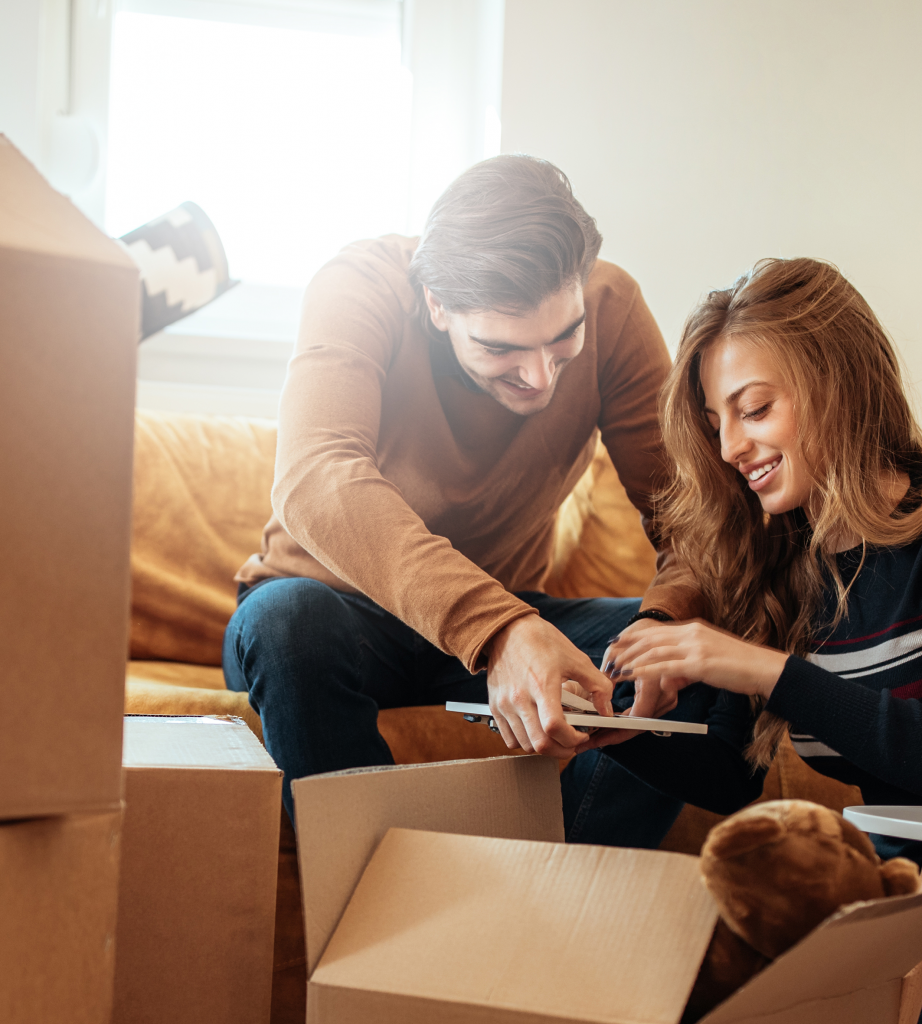 Couple packing books in to moving boxes